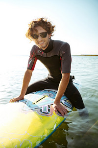 Smiling young male surfer sitting on his surf board in water wearing swimsuit and looking at camera