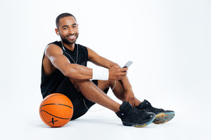 Smiling young man basketball player sitting and listening to music from smartphone over white background
