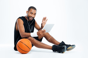 Smiling young man basketball player sitting and listening to music from tablet over white background