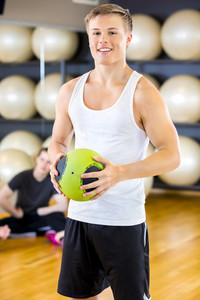 Smiling young man holding a slam ball at fitness gym