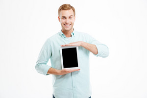 Smiling young man holding blank screen tablet over white background
