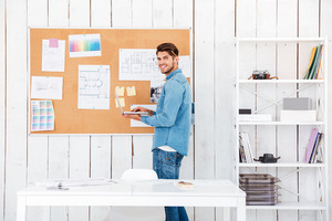 Smiling young man holding laptop and standing at task board in office