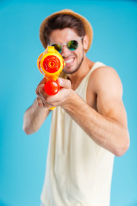 Smiling young man in hat and sunglasses playing with water gun over blue background