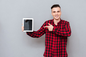 Smiling young Man in shirt showing blank tablet screen and pointing on him. Isolated gray background