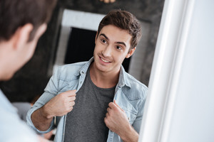 Smiling young man looking at himself in a mirror and holding his open shirt with two hands