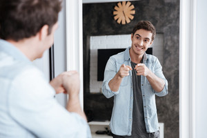 Smiling young man pointing fingers at his mirror reflection while standing at home