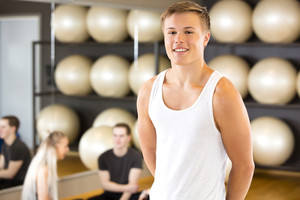 Smiling young man portrait at fitness gym