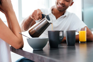 Smiling young man pouring coffee into cups and having breakfast with his girlfriend at home
