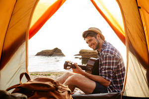 Smiling young man sitting near touristic tent and playing guitar at the beach