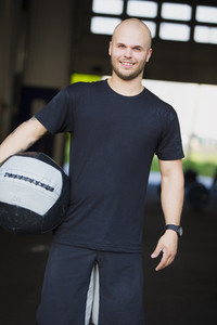 Smiling young man with med-ball at the fitness gym