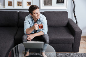 Smiling young man working on laptop and holding cup of tea at home