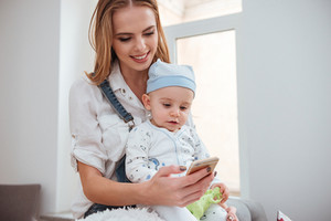 Smiling young mother holding her little son and using cell phone at home