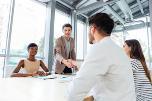 Smiling young people shaking hands on business meeting in office