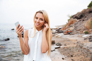 Smiling young pretty woman listening music with smartphone while standing at the rocky beach