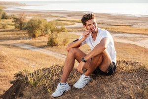 Smiling young sportsman resting and listening music with earphones after workout outdoors