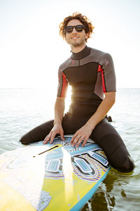 Smiling young surfer man in eyeglasses sitting on surf board in ocean and looking away