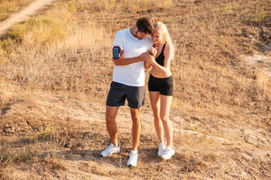 Smiling young woman and personal trainer with smartphone outdoors having break
