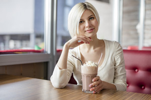 Smiling young woman drinking hot chocolate with cream at cafe