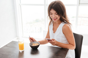 Smiling young woman having breakfast and using cell phone on the kitchen