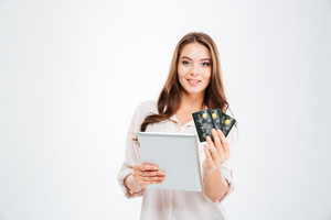Smiling young woman holding bank card and tablet computer isolated on a white background