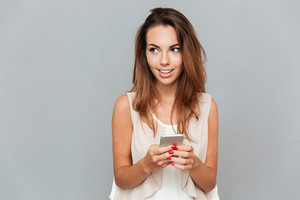 Smiling young woman holding mobile phone isolated on a gray background