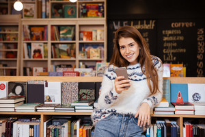 Smiling young woman holding mobile phone while sitting in library