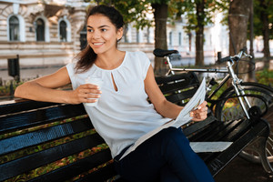 Smiling young woman holding newspaper while sitting on the bench with cup of coffee