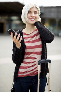 Smiling Young Woman Holding Smart Phone Outside Railroad Station