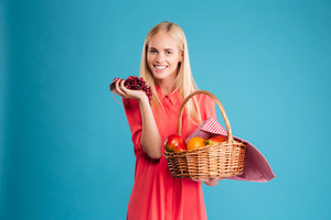 Smiling young woman holding straw basket with healthy food fruits isolated on a blue background