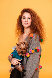 Smiling young woman hugging a dog isolated on orange background