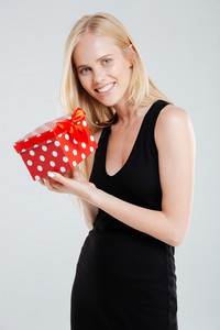 Smiling young woman in black dress holding gift box isolated on a white background