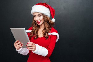 Smiling young woman in red christmas costume using tablet over black background