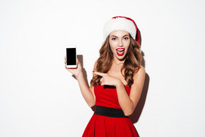 Smiling young woman in santa claus hat pointing finger at blank screen smartphone over white background