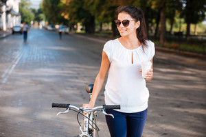 Smiling young woman in sunglasses walking with bicycle and takeaway coffee