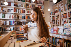 Smiling young woman in sweater reading book and drinking coffee in library