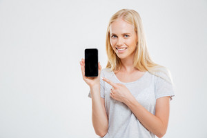 Smiling young woman pointing finger at blank smartphone screen isolated on a white background