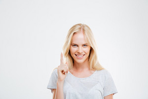 Smiling young woman pointing finger up over white background