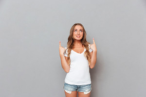 Smiling young woman pointing two fingers up over gray background