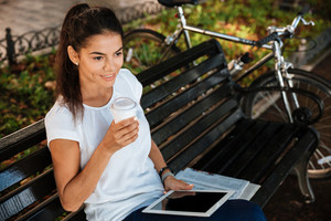 Smiling young woman resting on the bench with cup of coffee at the city park and holding tablet