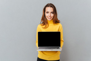 Smiling young woman showing blank laptop computer screen isolated on a gray background