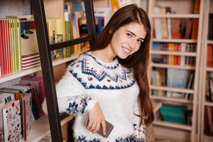 Smiling young woman standing at the book shelf with mobile phone and looking at camera