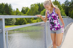 Smiling young woman stretching outdoor on a bridge