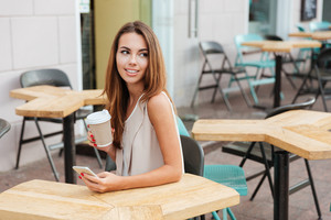 Smiling young woman using cell phone and drinking coffee in outdoor cafe