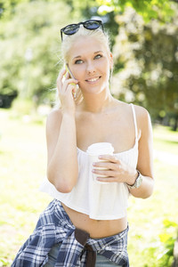 Smiling young woman with phone and coffee in park