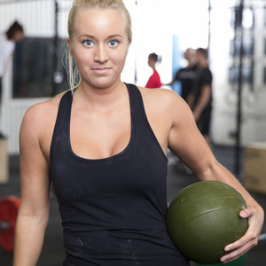 Smiling young woman with slam ball at gym center