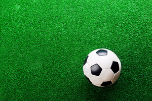 Soccer ball against artificial turf, studio shot on green background. Copy space.