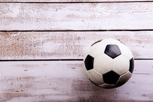 Soccer ball against wooden floor, studio shot on white background. Copy space.