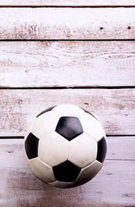 Soccer ball against wooden floor, studio shot on white background. Copy space.