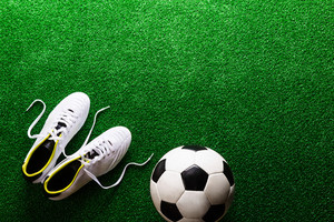 Soccer ball and cleats against artificial turf, studio shot on green background. Copy space.