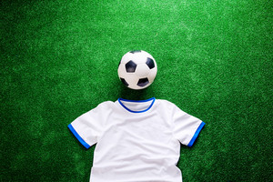 Soccer ball and white t-shirt against artificial turf. Studio shot on green background. Flat lay. Copy space.